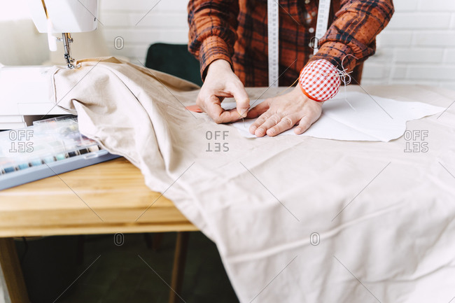 Close-up of woman pinning sewing pattern on table at home