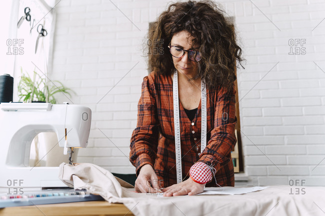 Woman pinning sewing pattern on table at home