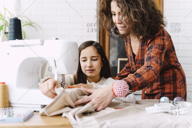 Mother and daughter sewing at home