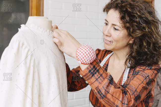 Woman pinning top on dress form at home