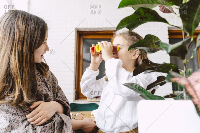 Two playful girls with spool at home
