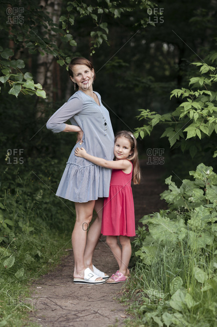 Portrait of smiling girl embracing pregnant mother at park