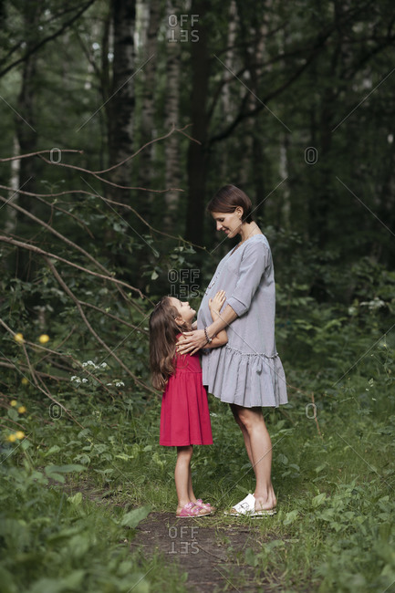 Pregnant woman standing with daughter against trees at park