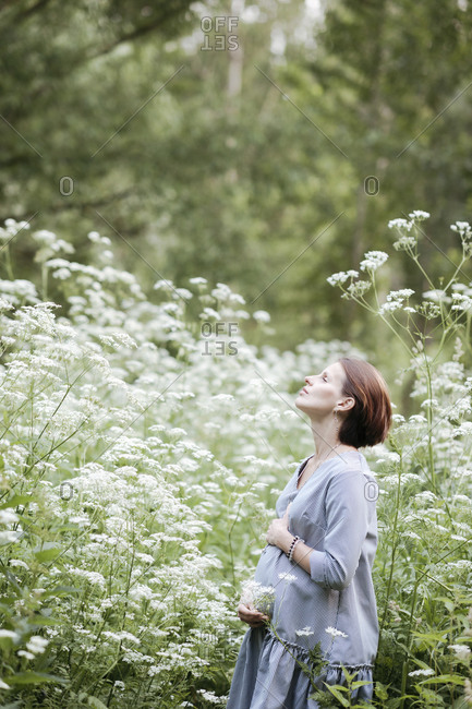 Pregnant woman with hands on stomach relaxing amidst flowers in park