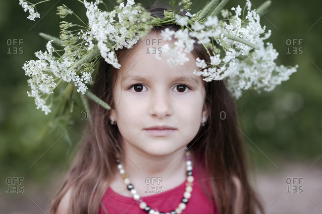 Portrait of cute girl wearing white flowers at park