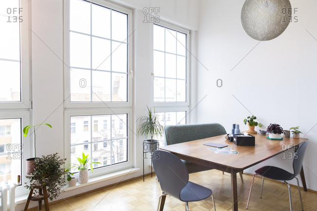 Dining table in bright living room with large windows
