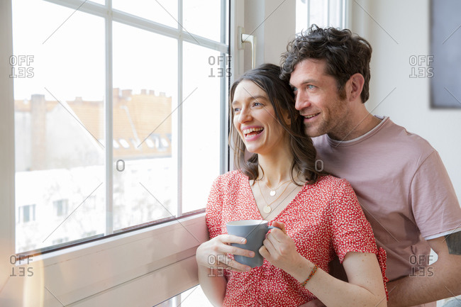 Happy couple at home looking out of window