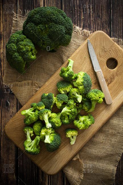 Place mat- cutting board- kitchen knife and fresh broccoli