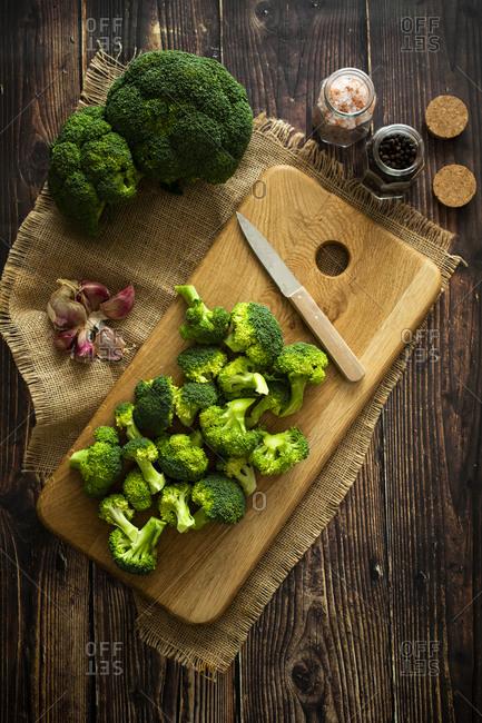 Place mat- salt and pepper- cutting board- kitchen knife- garlic- and fresh broccoli
