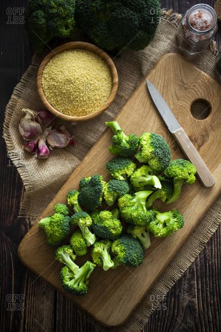 Place mat- cutting board- salt- garlic- bowl of couscous-kitchen knife and fresh broccoli