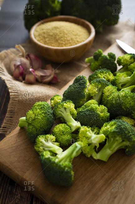 Cutting board- garlic- bowl of couscous- and fresh broccoli