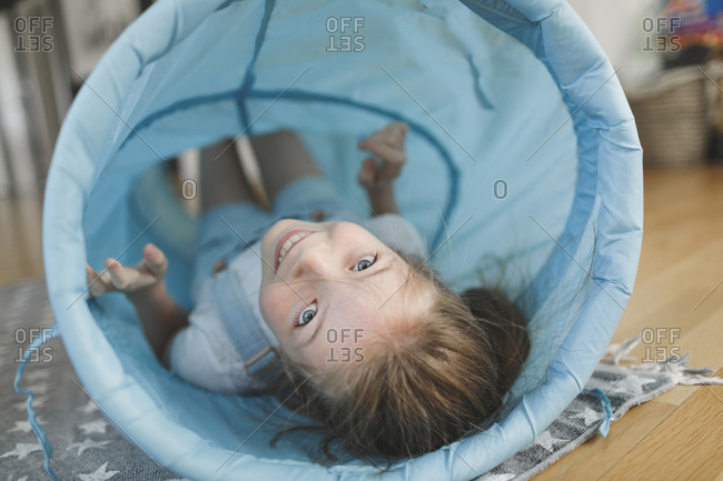 Smiling girl playing with blue fabric tunnel at home