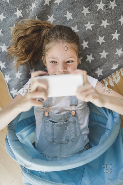 Portrait of smiling girl lying in blue fabric tunnel on the floor at home taking selfie with mobile phone