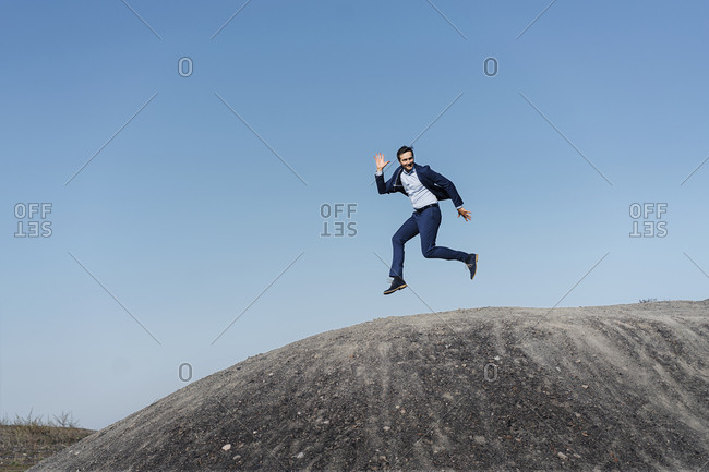 Mature businessman jumping on a disused mine tip