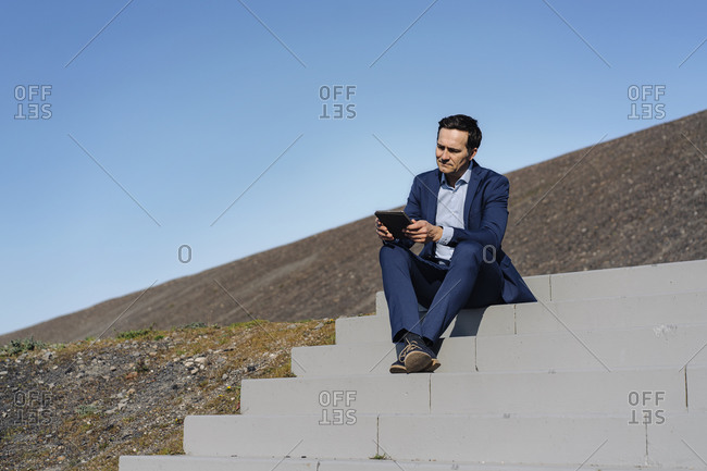 Mature businessman sitting on stairs on a disused mine tip using tablet