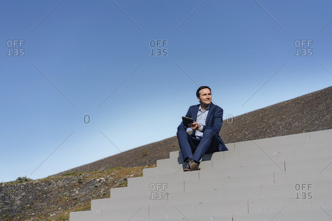 Mature businessman sitting on stairs on a disused mine tip holding tablet