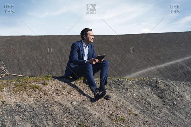 Mature businessman sitting on a disused mine tip holding tablet