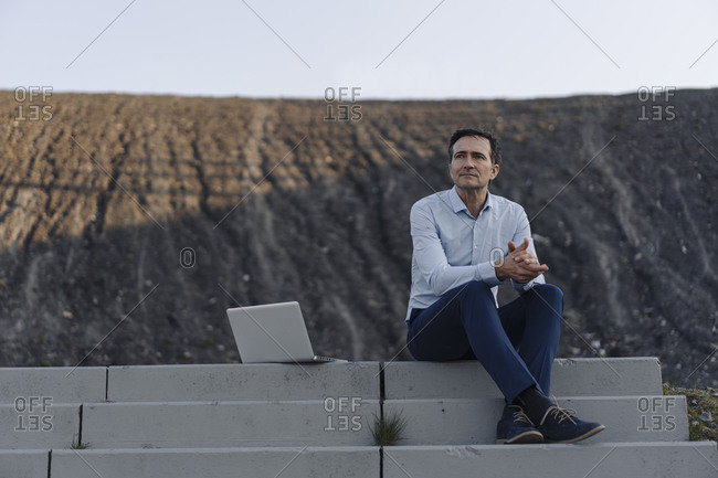 Mature businessman sitting on stairs on a disused mine tip next to laptop