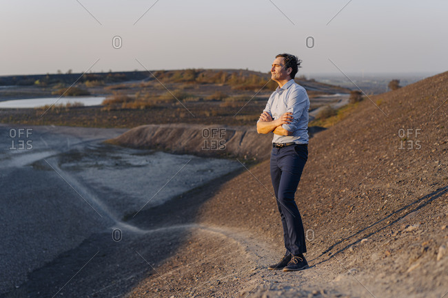 Mature businessman standing on a disused mine tip looking at view