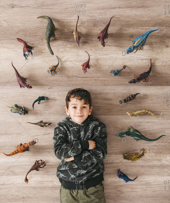 Portrait of smiling little boy lying on the floor between toy dinosaurs