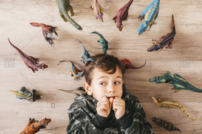 Portrait of anxious little boy lying on the floor between toy dinosaurs