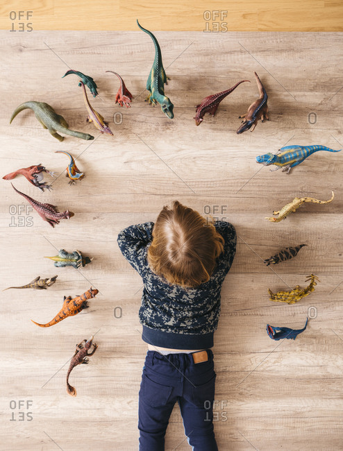 Little girl lying on the floor playing with toy dinosaurs around her- top view