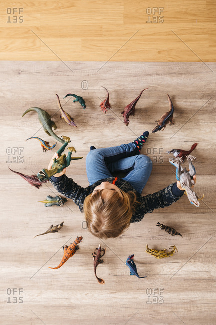 Little girl sitting on the floor playing with toy dinosaurs around her- top view