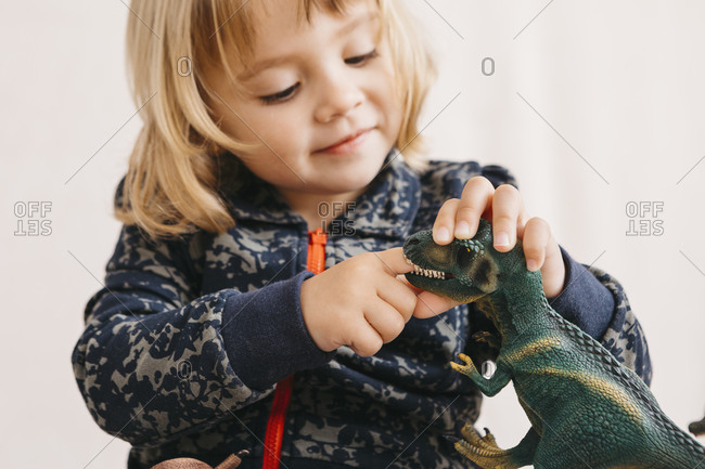 Smiling little girl playing with toy dinosaur