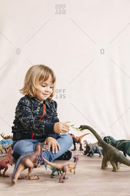 Portrait of cute little girl sitting on the floor feeding toy dinosaur