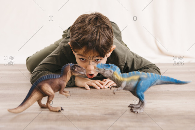 Portrait of little boy crouching on the floor playing with toy dinosaurs