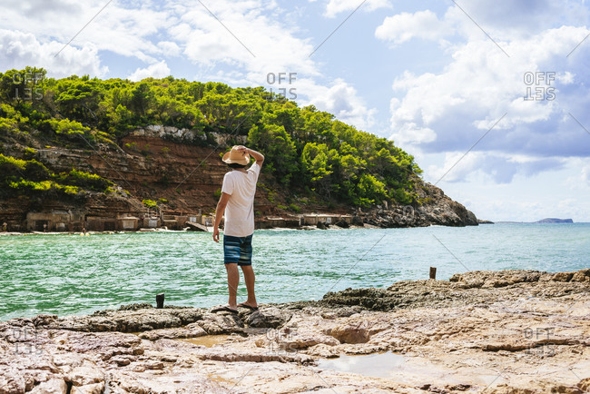 Back view of man standing on cliff looking to sea- Cala Benirras- Ibiza- Spain