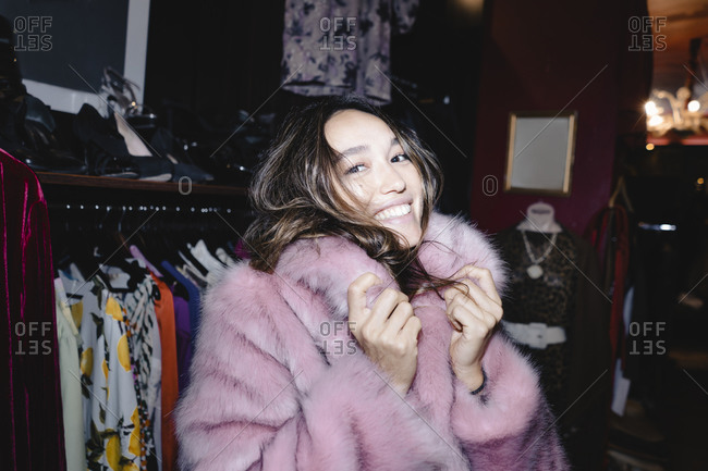 Portrait of smiling woman wearing pink fur jacket at thrift store