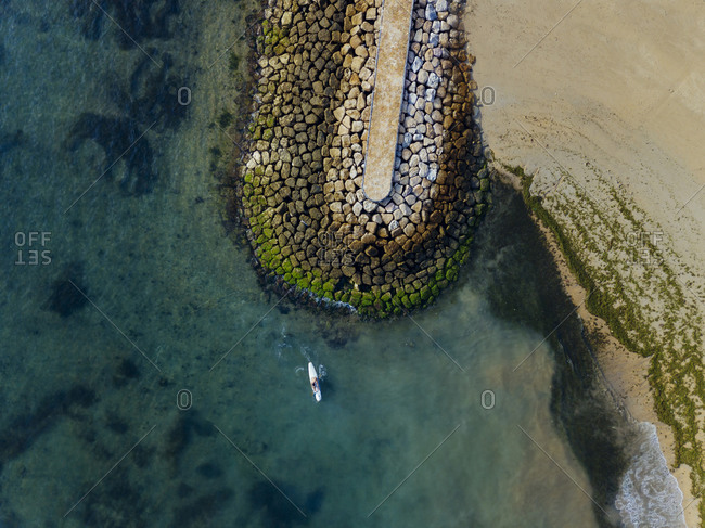Indonesia- Bali- Sanur- Aerial view of lone surfer in front of rocky coastline