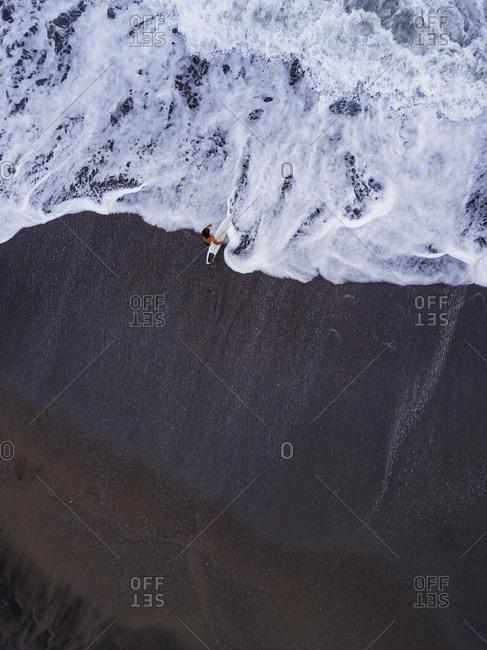 Indonesia- Bali- Pererenan Beach- Aerial view of lone surfer at black coastal beach