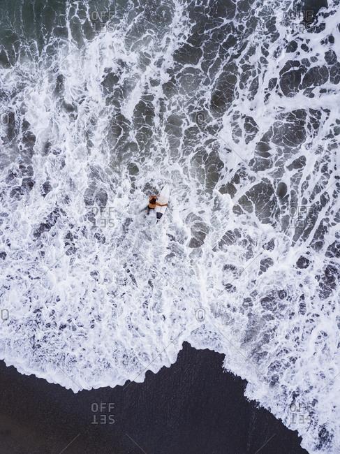 Indonesia- Bali- Pererenan Beach- Aerial view of lone surfer entering water