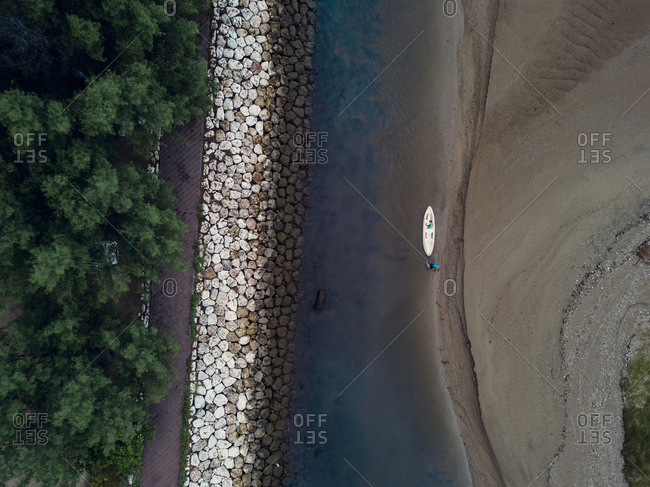 Indonesia- Bali- Sanur- Aerial view of man with canoe at sandy riverbank