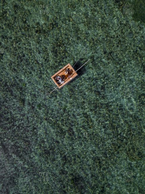 Indonesia- Bali- Nusa Dua- Aerial view of two people fishing on boat near Gunung Payung Beach