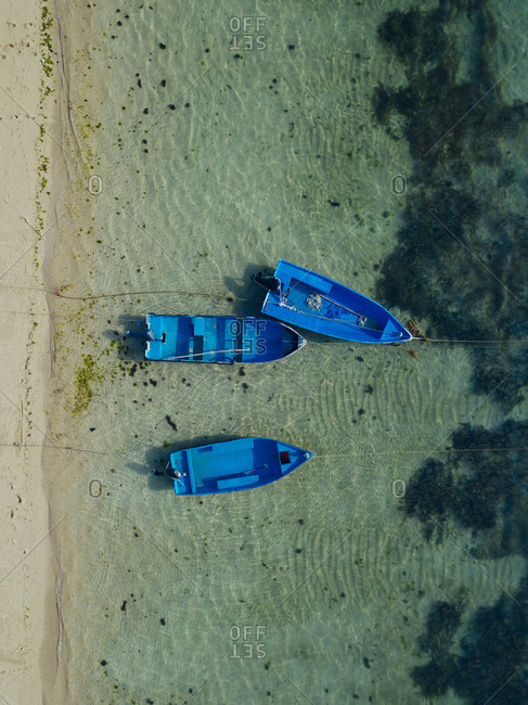 Indonesia- Bali- Sanur- Aerial view of blue boats moored in front of sandy coastal beach