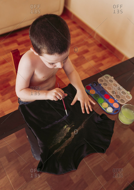 High angle view of shirtless boy drawing on t-shirt with watercolor paints at home