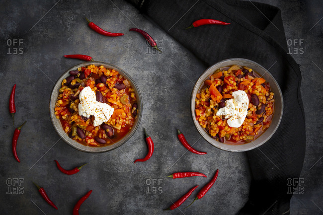 Red chili peppers and two bowls of vegetarian chili with red lentils- kidney beans- tomatoes- carrots- celery and sour cream
