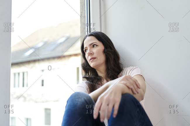 Thoughtful female professional in smart casuals looking through window at office