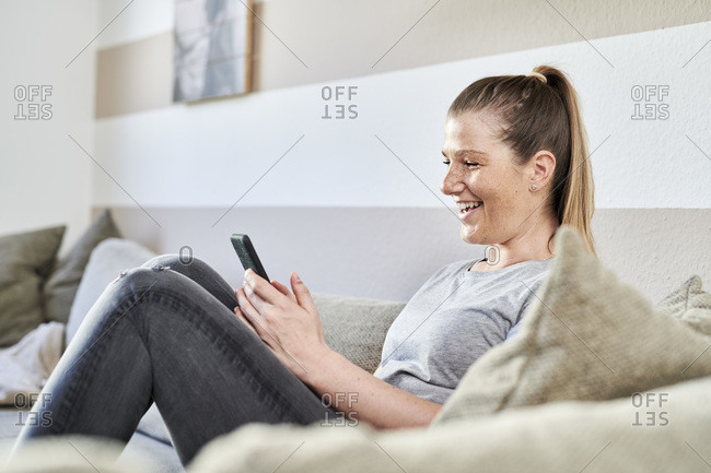 Smiling woman using smart phone while sitting on sofa at home