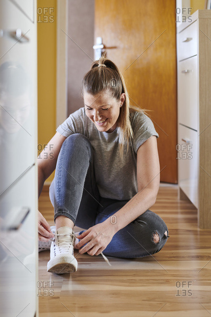 Smiling woman tying shoelace while sitting on hardwood floor at home
