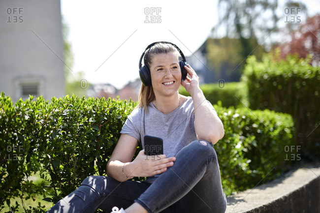 Smiling woman looking away while listening music through headphones on smart phone by plants