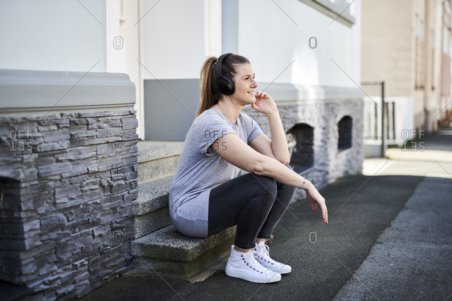 Woman listening music on wireless headphones while sitting on steps