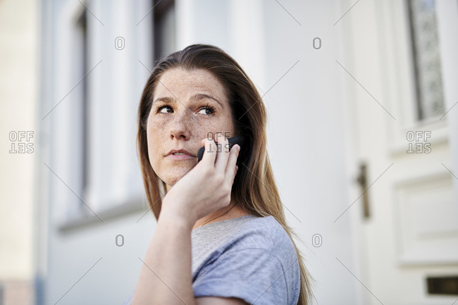 Woman looking away while talking on smart phone against house
