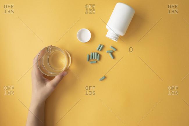 Studio shot ofnutritional supplement capsulesand hand of woman picking up glass of water