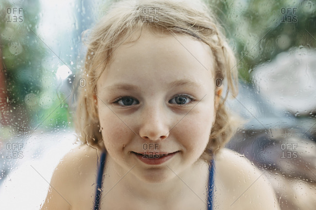 Portrait of smiling blond girl looking through wet windowpane
