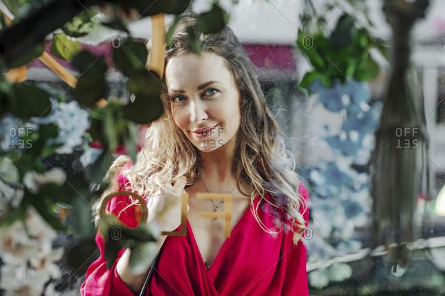 Portrait of a woman behind windowpane of a flower shop