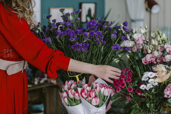 Close-up of woman touching flowers in flower shop